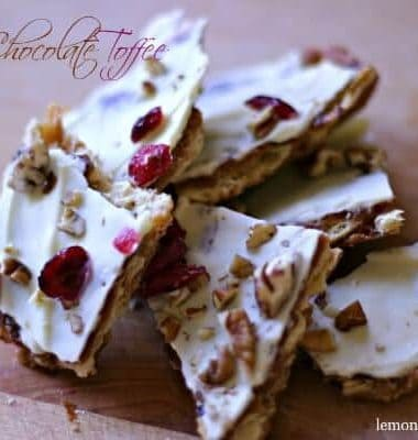 Simple saltine toffee with white chocolate, cranberries and pecans on a wooden table.