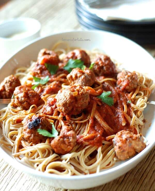 Meatballs and Spaghetti in a white serving bowl.