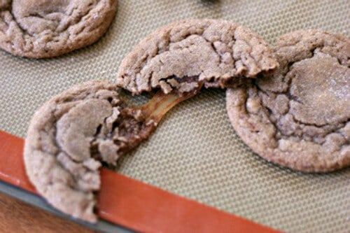 Nutella cookies stuffed with Milk Dud Candies on a baking sheet.