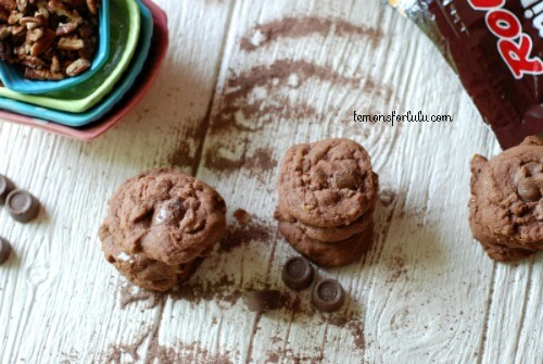Chocolate turtle pudding cookies surrounded by rolos on a white wooden table.
