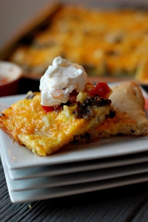 Two delicious slices of Breakfast Pizza with protein filled greek yogurt on top of four white serving dishes.