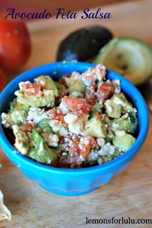 Avocado Feta Salsa recipe with tomatoes and feta cheese in a small blue bowl on a wooden table.
