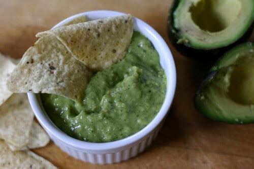 Delicious Avocado Salsa Verde recipe with two tortilla chips inside of a small white bowl on a wooden table.