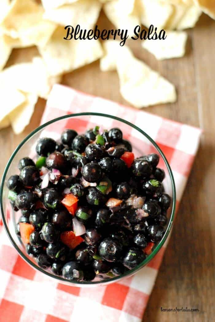 Blueberry Salsa recipe with blueberries, bell peppers and cilantro on a red and white cloth on a wooden table.