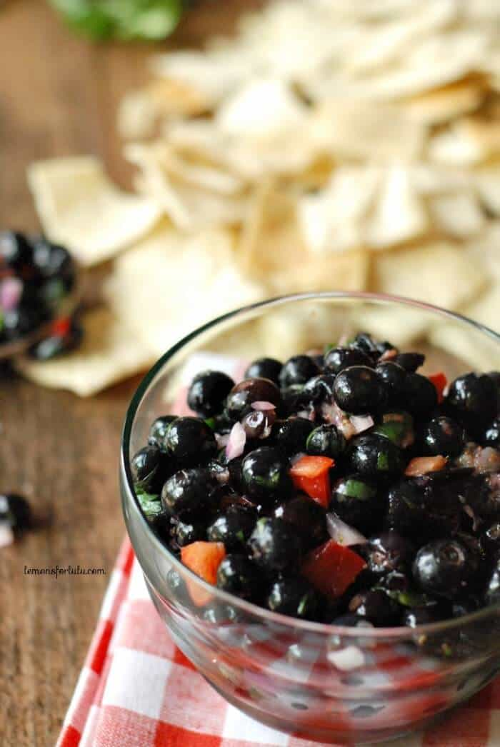 A delicious Blueberry Salsa with cilantro, bell pepper, blueberries and red onion in a clear glass bowl with tortilla chips in the background.