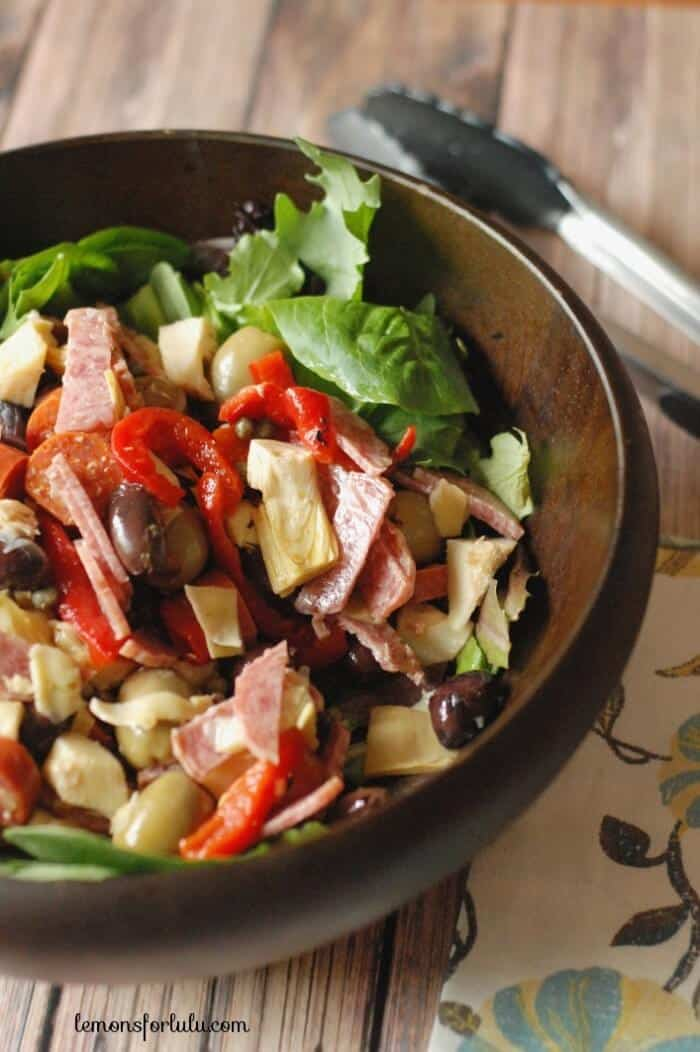 A simple antipasto salad with two kinds of olives, roasted red peppers, artichokes and a tangy feta vinaigrette www.lemonsforlulu.com
