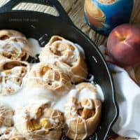 This cinnamon roll recipe is so easy, you will fall in love! A cast iron skillet, fresh peaches and crescent roll dough makes them irresistible! www.lemonsforlulu.com