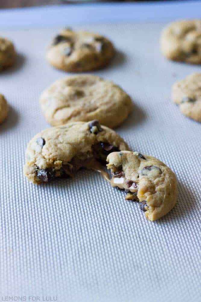 These pumpkin cookies are soft and tender and loaded with chocolate chips! Each cookies has a caramel filled center dusted wtih a hint of sea salt www.lemonsforlulu.com
