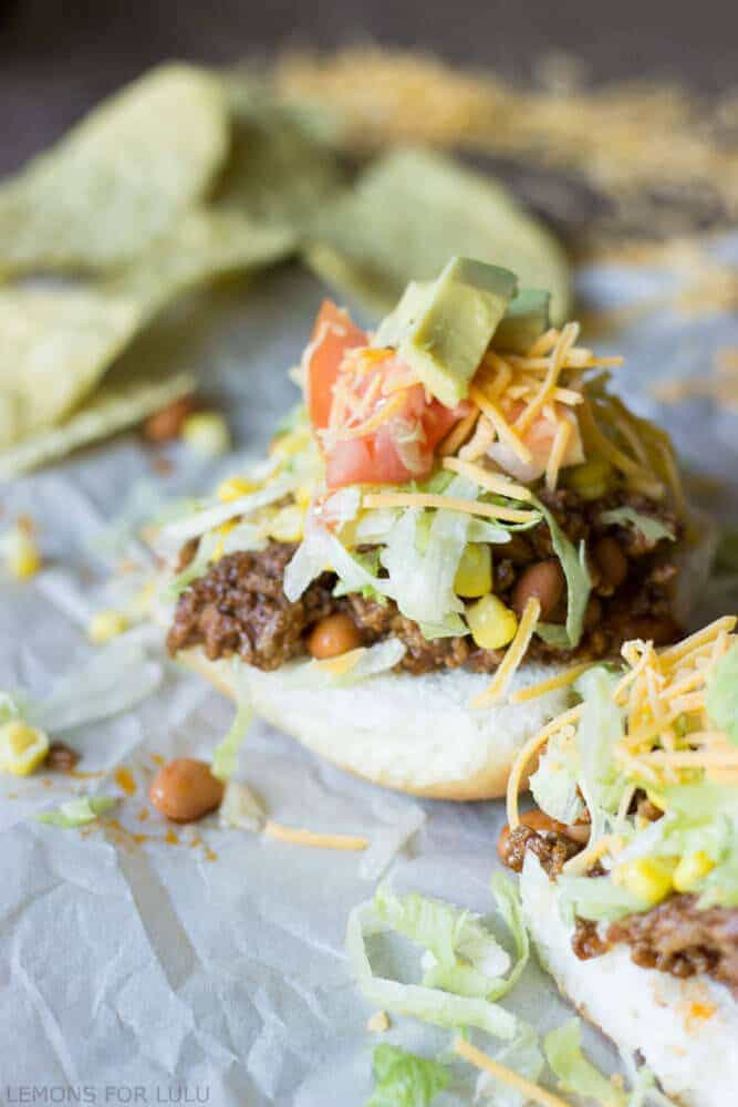 Easy and simple taco sloppy joes with fresh avocado, cheese, sweet corn and tomatoes.