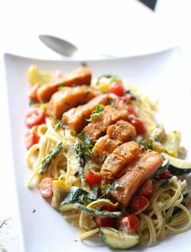 This salmon topped pasta Primavera is filled with veggies and tossed with a light, creamy sauce. A simple, elegant meal for any occasion. lemonsforlulu.com