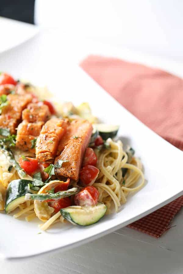 Veggie packed pasta Primavera is topped with seasoned salmon . lemonsforlulu.com