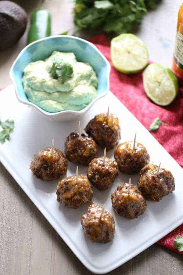 A baked meatball recipe with a sweet cocktail sauce and a cool and creamy avocado dipping sauce! Perfect party food! lemonsforlulu.com