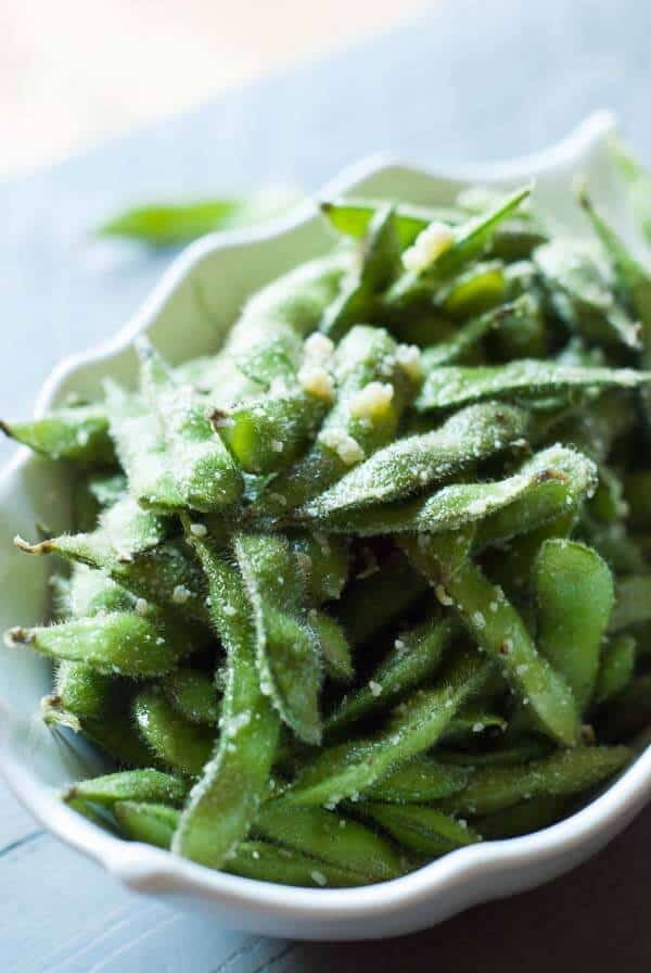 Edamame is steamed then coated in olive oil, garlic and Parmesan Cheese!  Enjoy these pods as a side or even as a snack! lemonsforlulu.com