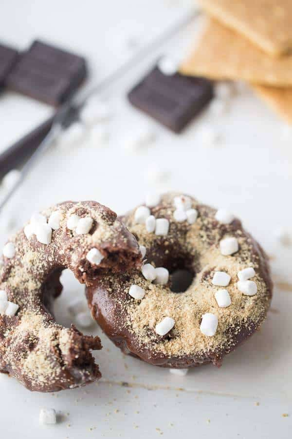 This baked donut recipe is the best! Chocolate donuts are double dipped and then topped with mini marshmallows and graham cracker crumbs! A S'mores breakfast treat! lemonsforlulu.com