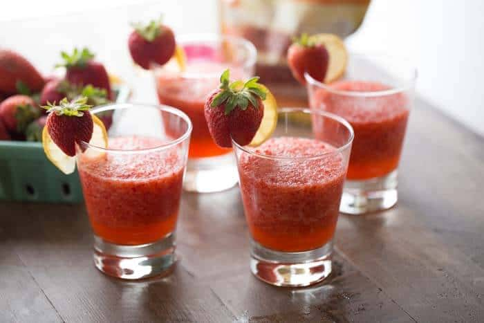 Four easy Strawberry rickey mocktails with fresh strawberries and lemons on a wooden table.