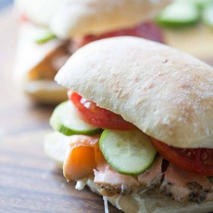 This easy Asian salmon recipe features seasoned salmond, fresh vegetables and wasabi mayo piled on a soft bakery style bread roll! lemonsforlulu.com