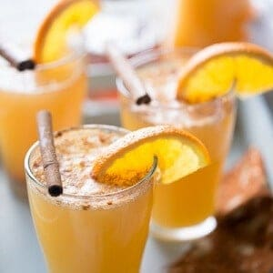 Three beer glasses of simple ginger beer with sliced oranges and cinnamon sticks.