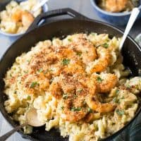 Cast iron skillet with Cajun Shrimp Mac and Cheese with a silver spoon on a wooden table.