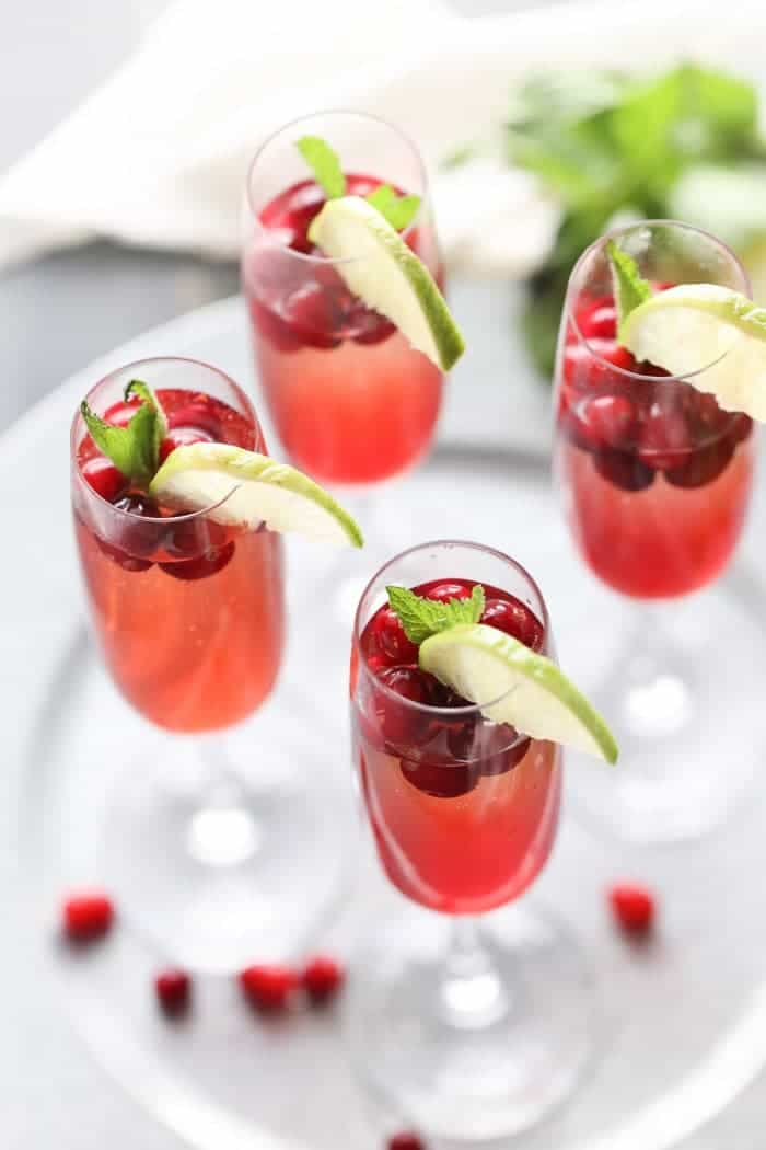 Champagne cocktail recipe with cranberry simple syrup, cranberry juice, vodka and of course champagne! lemonsforlulu.com