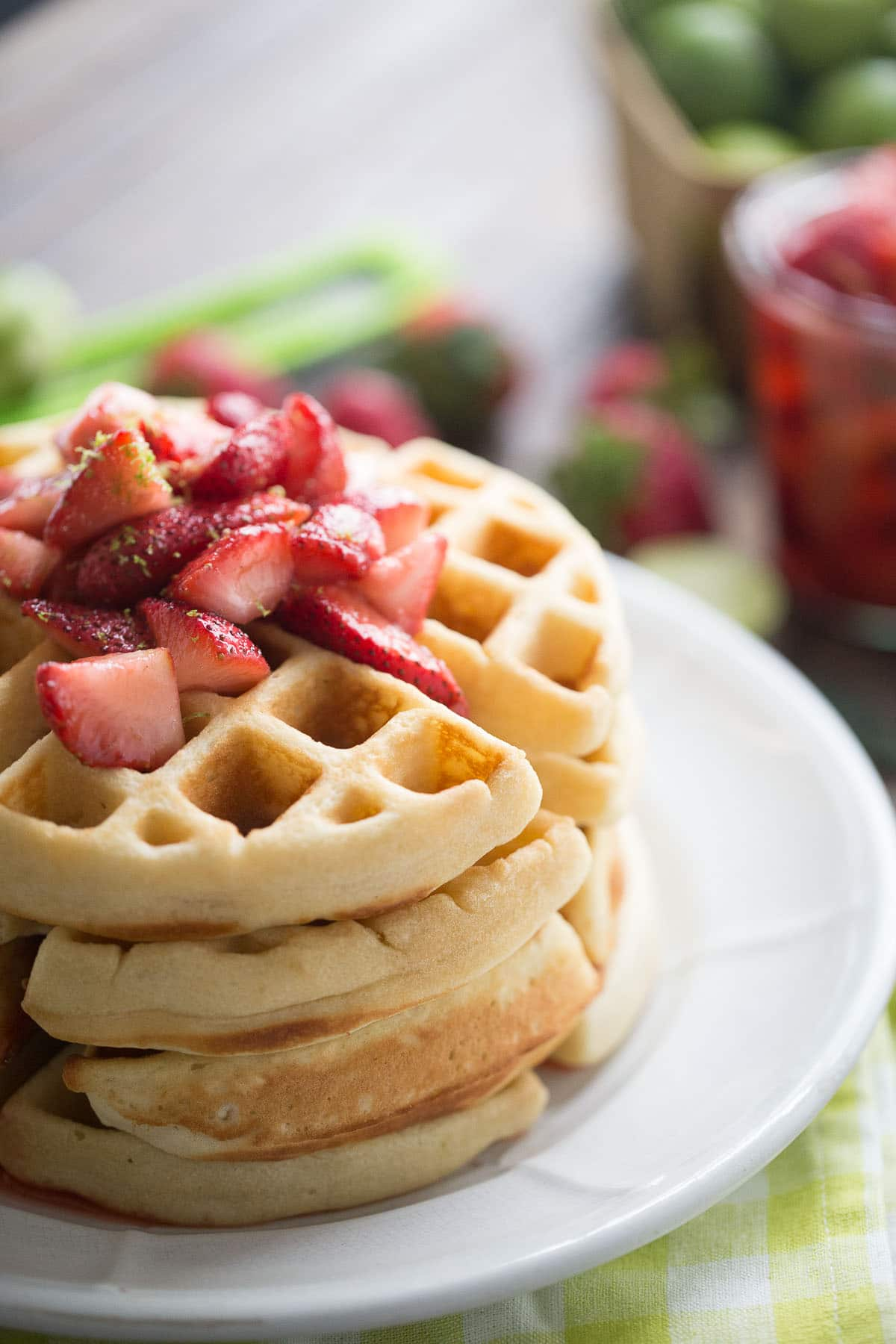 Who doesn't love waffles? This easy homemade waffles recipe is bursting with key lime flavor and is topped with a simple homemade strawberry sauce!