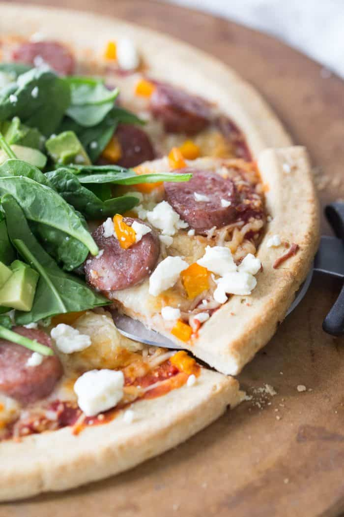 The pineapple bacon sausage tops the pizza along with veggies and a fresh pile of spinach, avocado and feta!