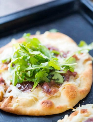 Naan bread is topped with creamy fontina cheese, salty prosciutto and sweet fig jam for this Naan Pizza recipe. | lemonsforlulu.com