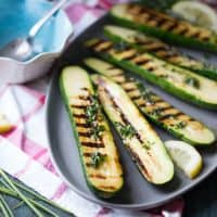 Grilled zucchini is drizzled with fresh herbs and butter for a satisfying side dish that everyone will love!