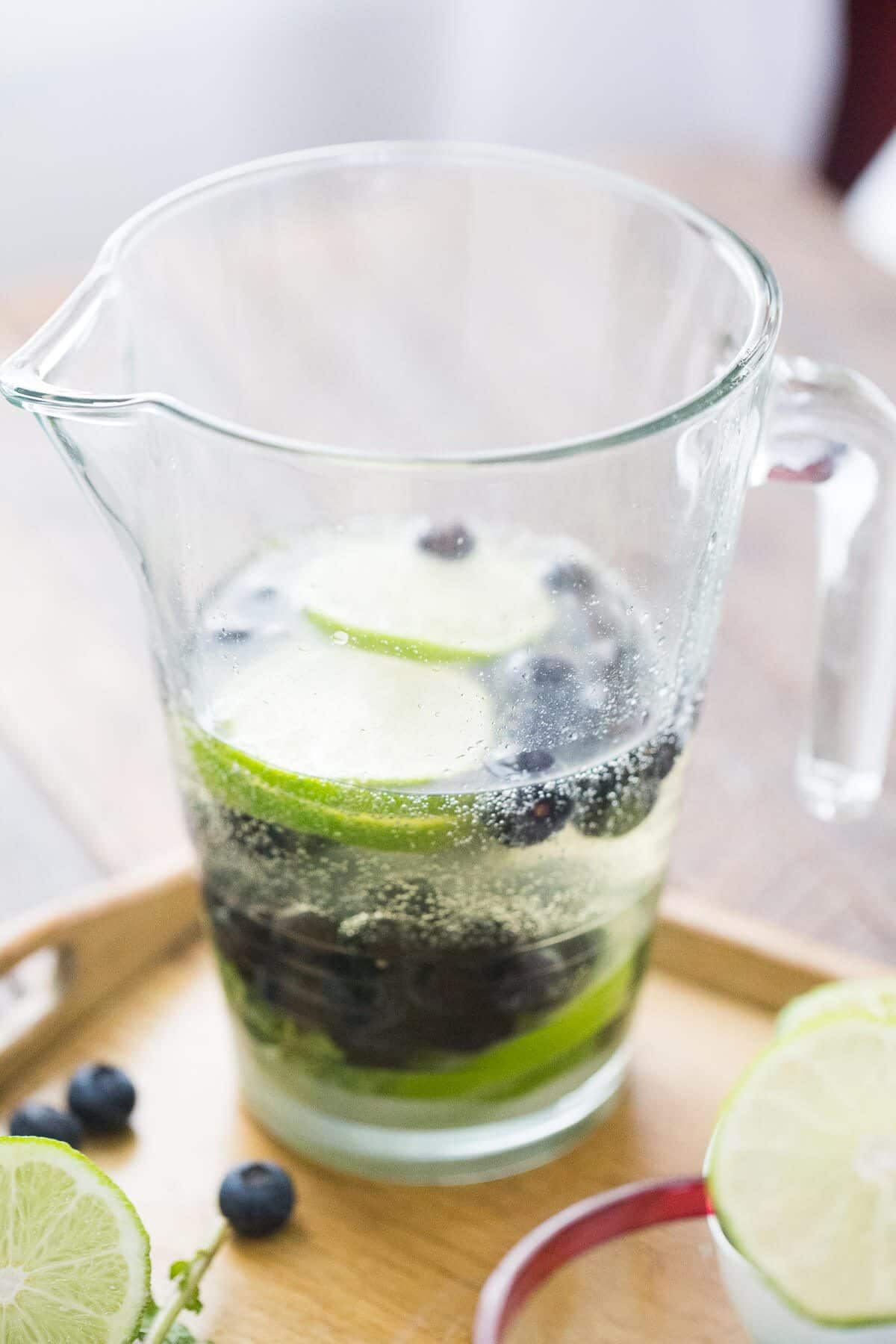 Homemade Blueberry Mojito in a pitcher with blueberries and sliced limes.
