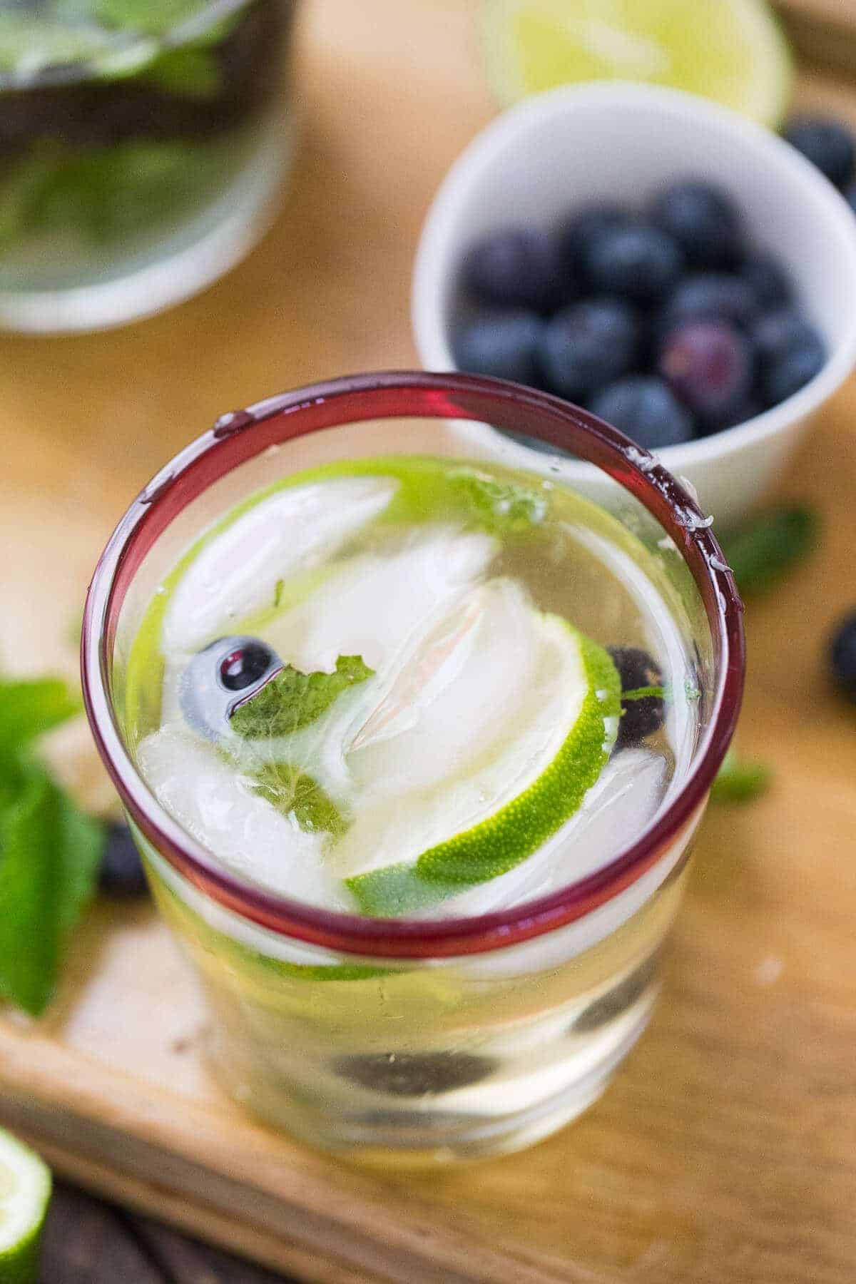Glass of a homemade Champagne Blueberry Mojito with ice, limes and blueberries.