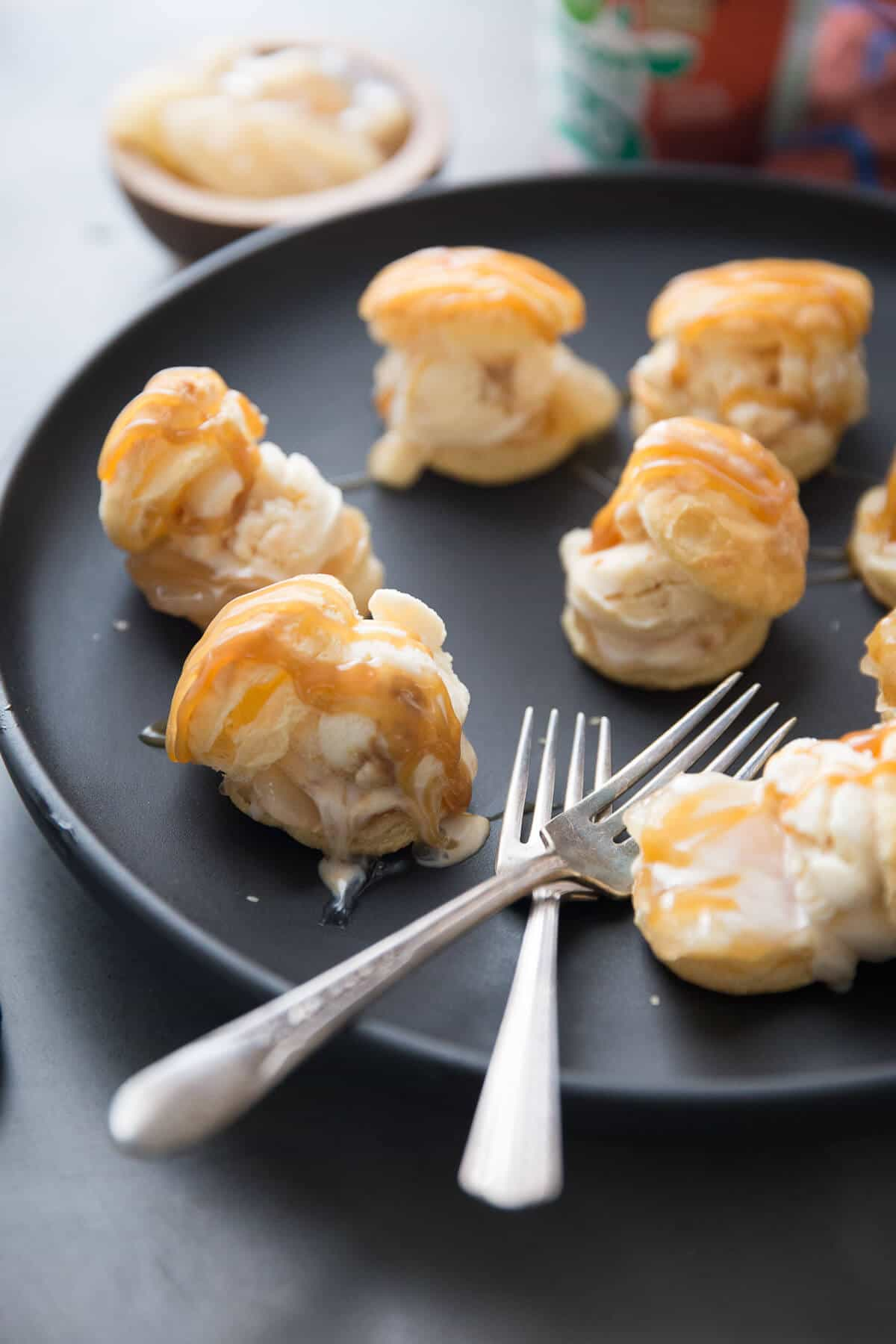 Six delicious profiteroles with vanilla ice cream and drizzled with yummy caramel on a black plate with two silver forks.