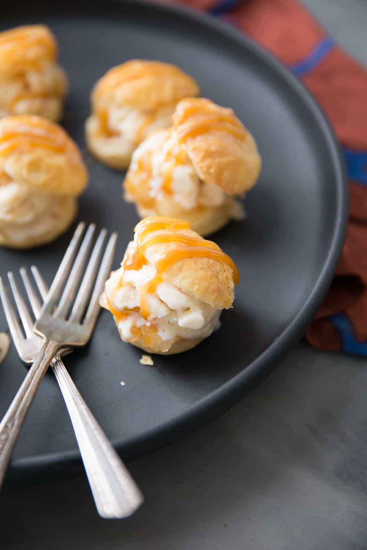 Five light and airy puff profiteroles on a black serving plate with two silver forks.