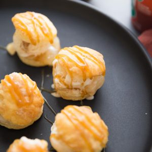 Light and airy puff pastry are the key to an easy profiterole! Apple pie filling and creamy salted caramel ice cream fill each delicate pastry.  This fancy sounding dessert is quick, easy yet so impressive!