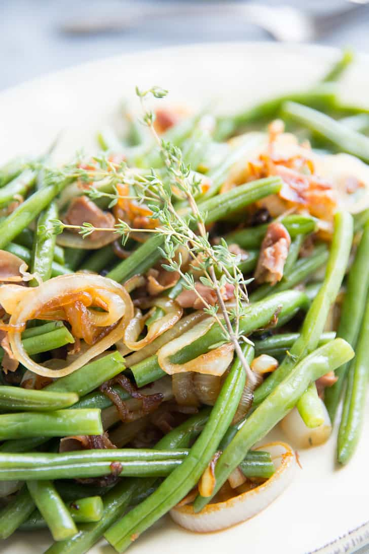 Closeup of Balsamic Green Beans with caramelized onions,, garnished with rosemary on a white serving platter.