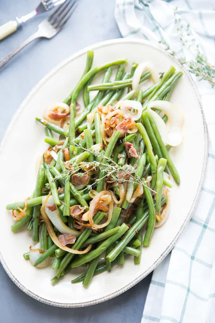 Delicious Balsamic Green Beans dish with caramelized onions on a white serving platter on a blue table.