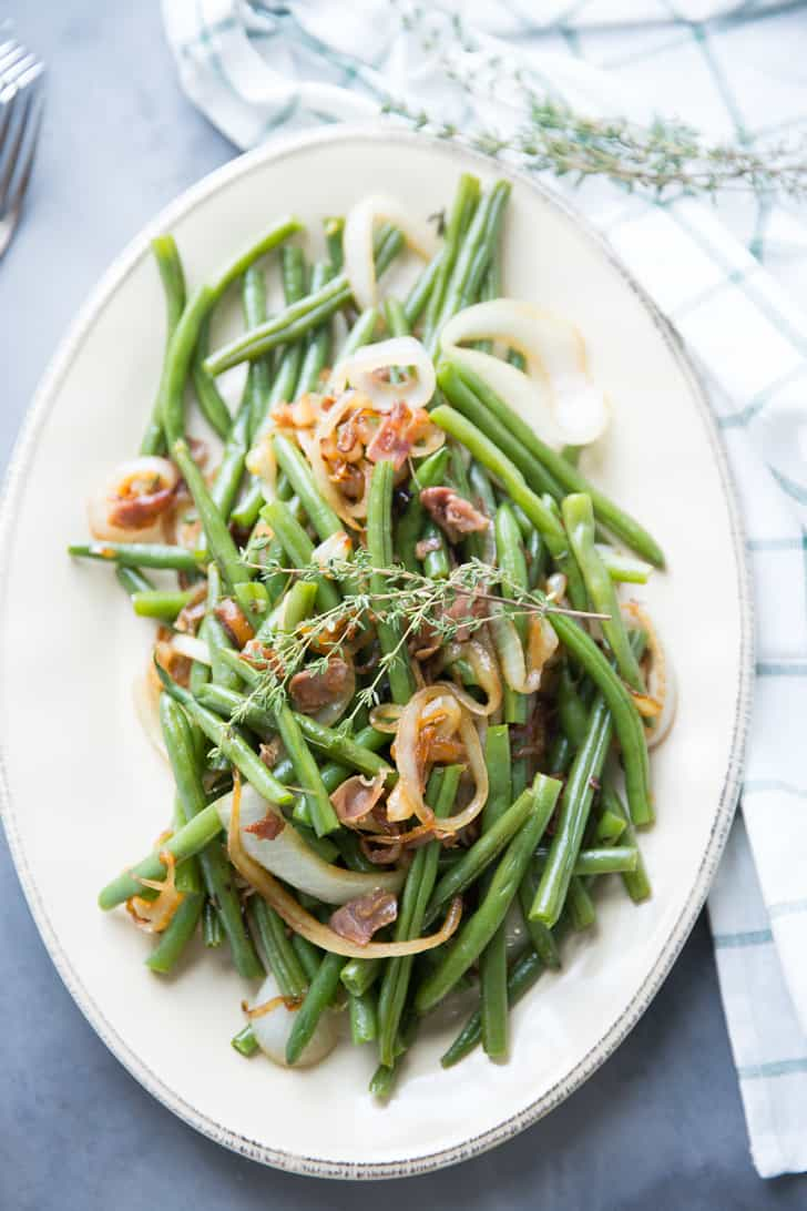 Delicious Green Beans with balsamic dressing with caramelized onions, garnished with rosemary on a white serving platter.