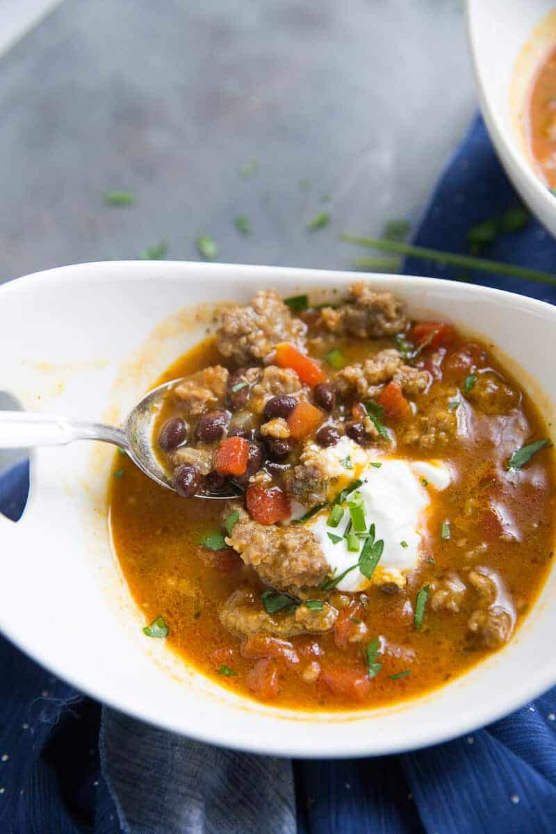 This black bean chili has a little something special; pumpkin!  This easy chili is filled with black beans, Italian sausage, spices, and pumpkin. This filling black bean chili is just what you need when you need a little warming!