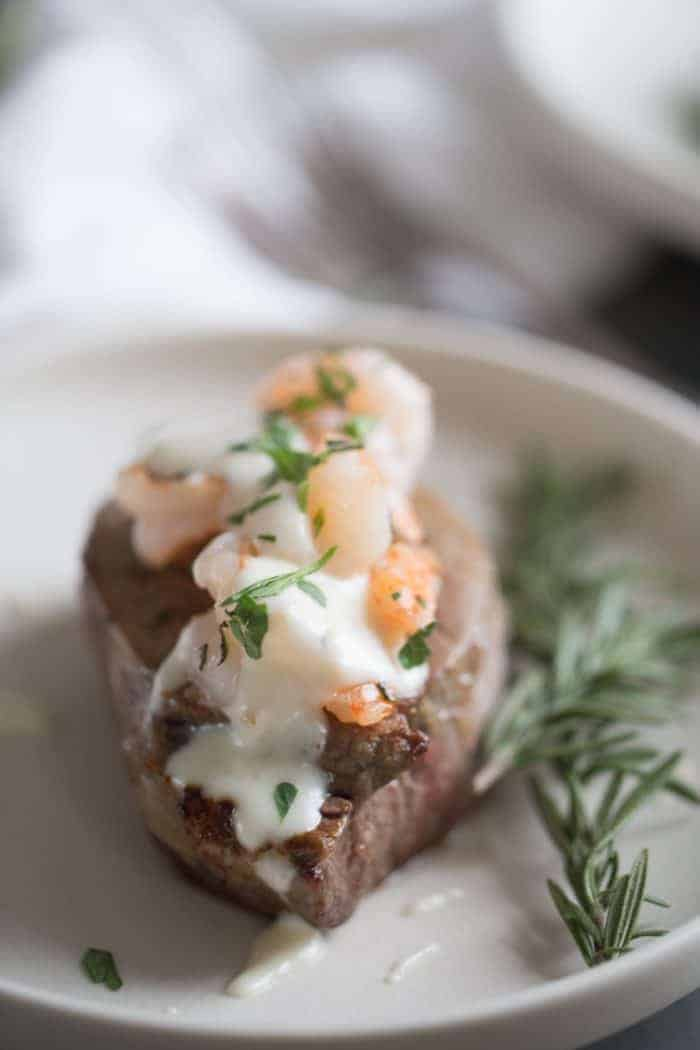 steak on a plate with shrimp on top