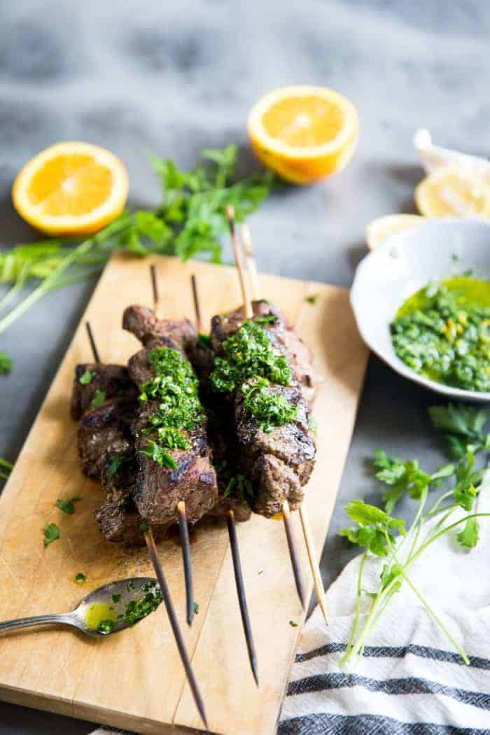 Beef shish kabobs with chimichurri sauce on beef and on the side