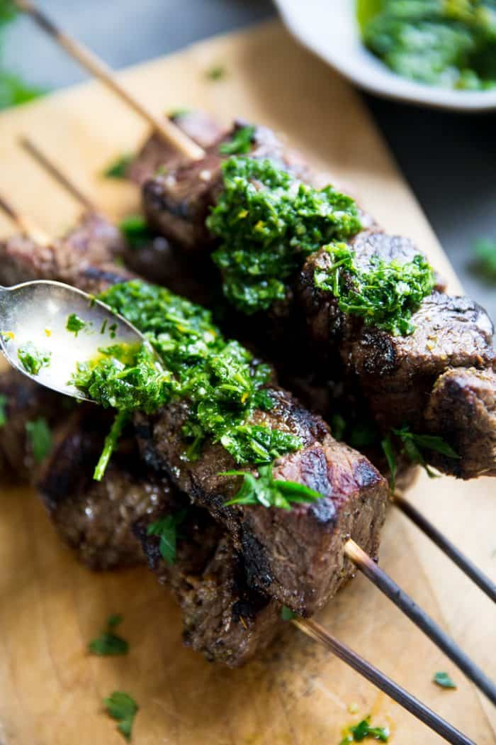 Beef shish kabobs spooning on chimichurri sauce