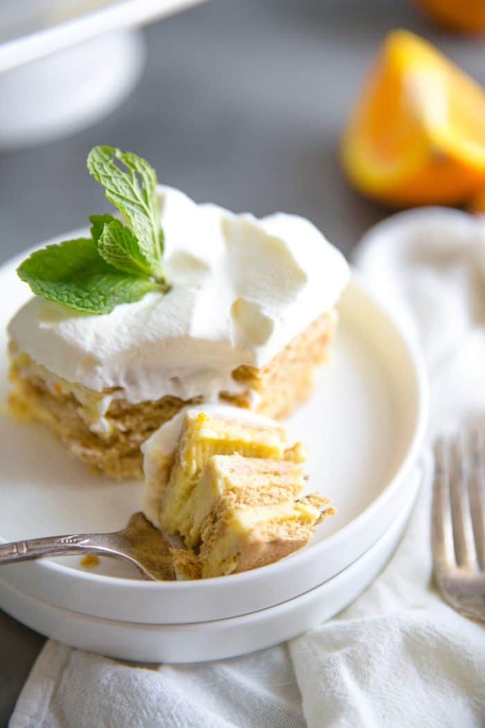 Orange creamsicle icebox cake slice with bite