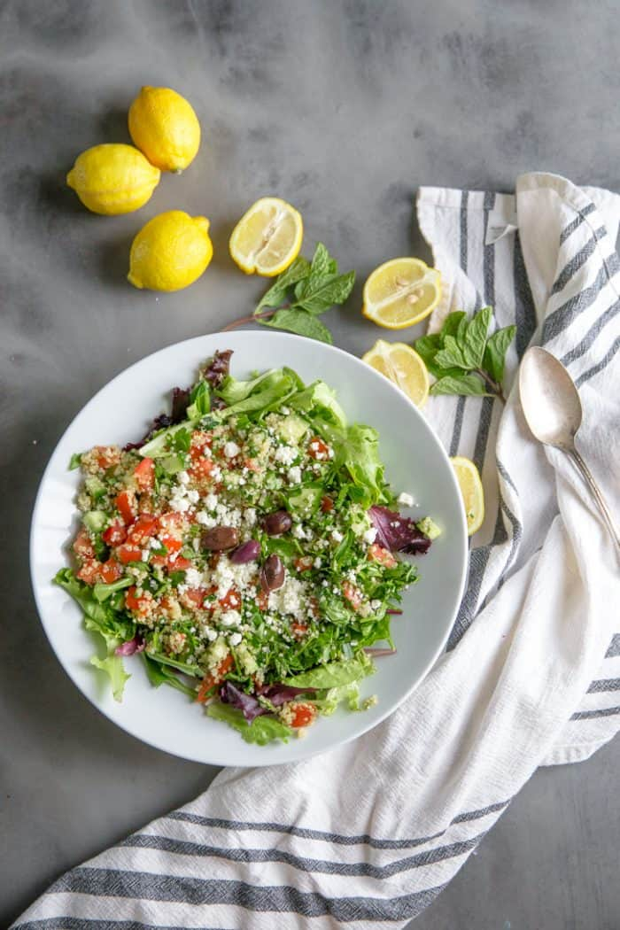 quinoa tabbouleh in a bowl surrounded by lemons