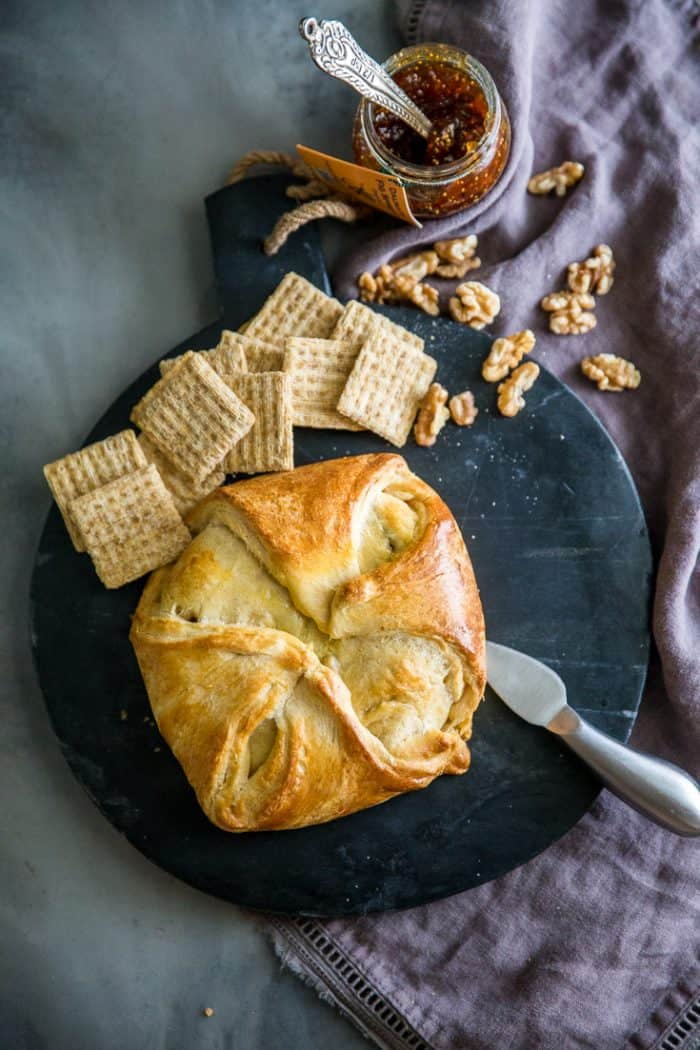 Baked brie appetizer whole on a black background