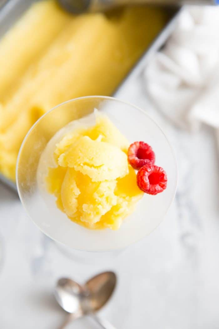 mango rum punch sorbet single glass with two raspberries