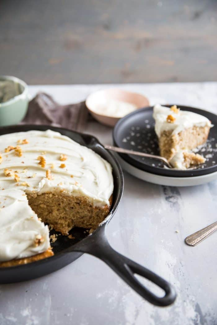 Hummingbird cake in skillet with one black plate