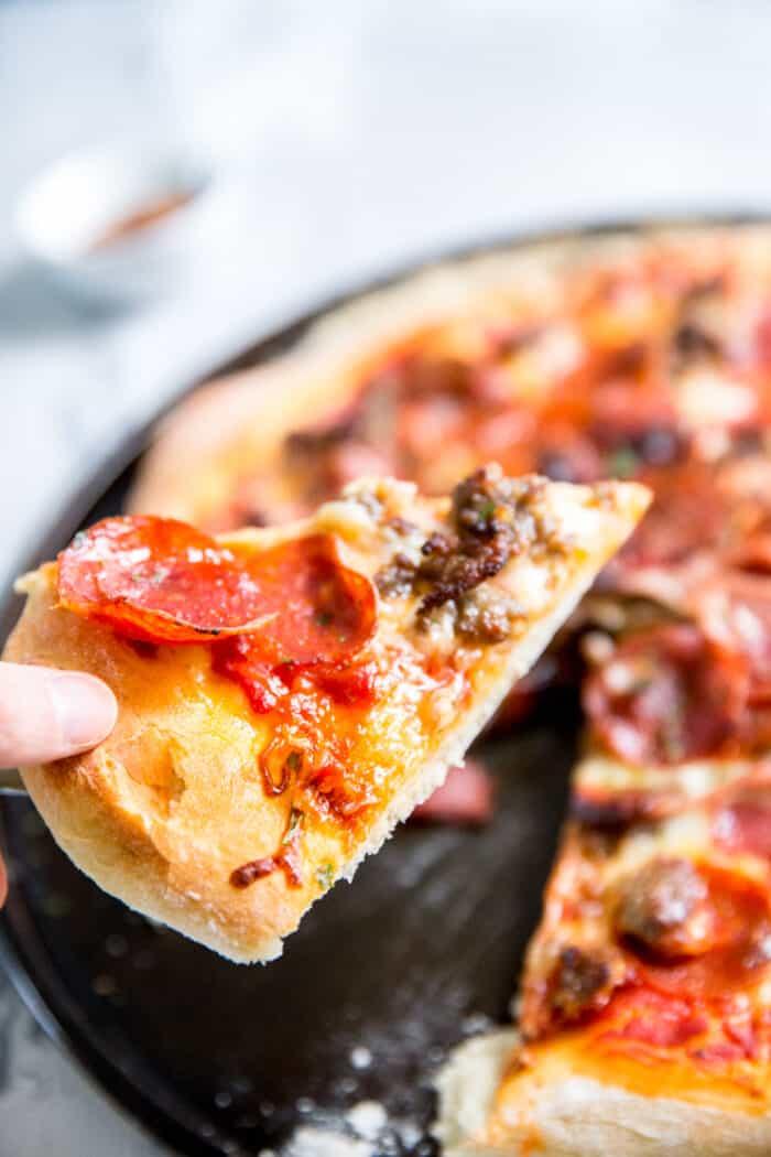 held Italian pizza slice