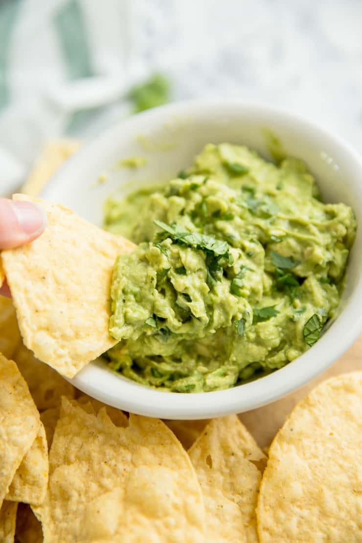 easy guacamole with a chip being dipped