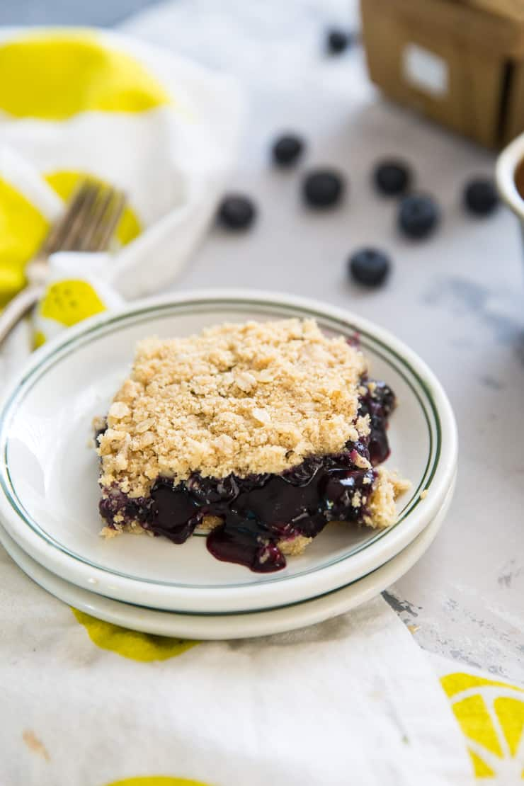 one slice of blueberry oatmeal bars on a plate with green rim