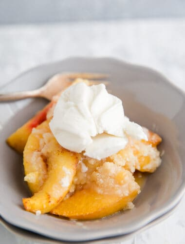 peach cobbler in a bowl with vanilla ice cream